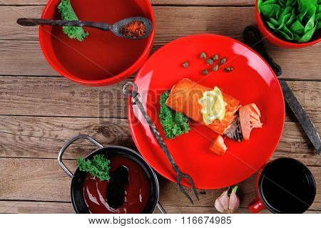 delicious portion of fresh roast salmon fillet on red plate with green salad kale tomato soup bbq sauce and black coffee over wooden table - healthy food, diet cooking concept