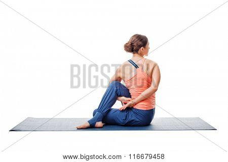 Beautiful sporty fit woman practices yoga asana  Ardha matsyendrasana - half spinal twist pose isolated on white