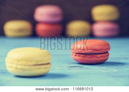 some appetizing macarons with different colors and flavors on a blue rustic wooden surface