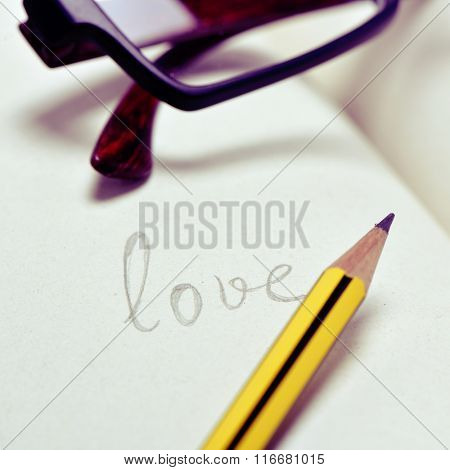 closeup of a pair of eyeglasses and the word love handwritten in a notebook with a pencil