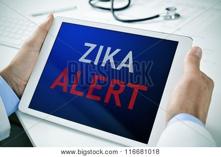 closeup of a doctor man sitting at his office desk holding a tablet computer with the text zika alert in its screen