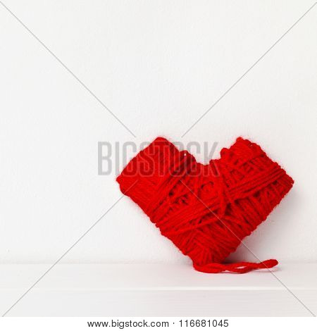 closeup of a heart-shaped coil of red yarn on a white surface against a white background