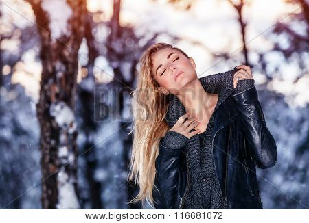 Portrait of gentle sexy blond female with closed eyes touching her neck in winter park, wearing stylish fashionable clothes