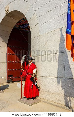 Seoul, Korea - March 8, 2015: Guard Stands At The Entry Gate Of Gyeongbokgung Palace, The Old Royal
