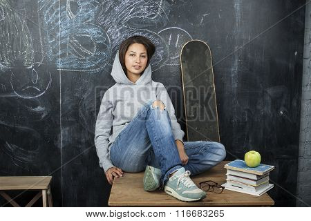 young cute teenage girl in classroom at blackboard seating on table smiling
