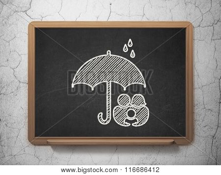 Protection concept: Family And Umbrella on chalkboard background