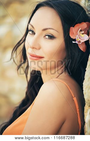 Beautiful Portrait Of A Young Brunette Woman With Orange Flower In Her Hair. Smiling Face
