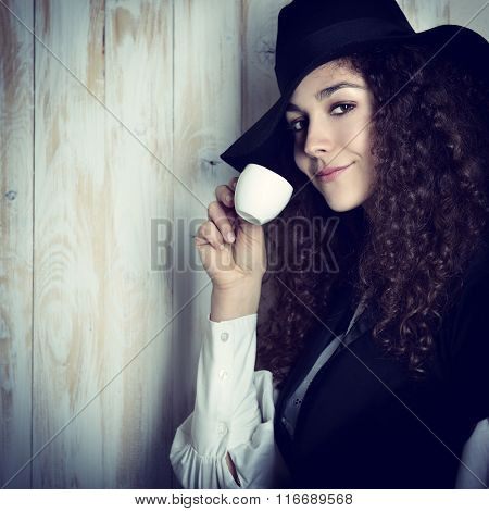 Young attractive woman with curly hair in retro dress and hat drinking coffee over wooden background. Vintage stylization of lady with cup of coffee smelling delicate aroma of beverage.