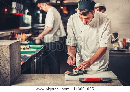 male cooks preparing sushi in the restaurant kitchen