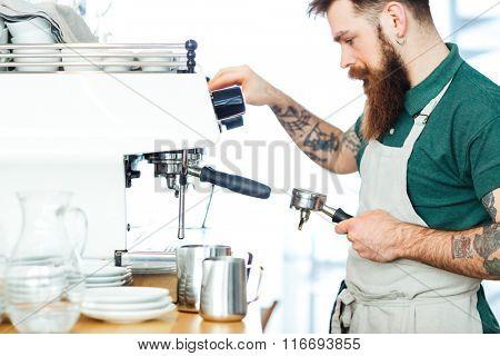 Male barista preparing coffee with coffee machine
