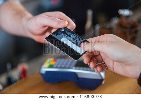 Closeup of two hands holding credit card for paying with reader