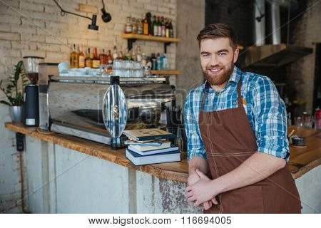 Portrait of cheerful bearded young waiter in brown apron standing in coffee shop