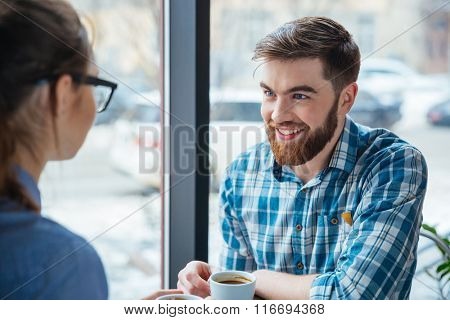 Cheerful handsome man sitting in cafe and drinking coffee with his girlfriend