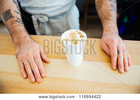 Cup with cappucino on the wooden table