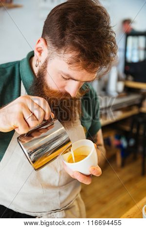 Barista pouring milk into cup of coffee at the coffee shop