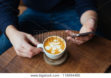 Closeup of cup of coffee with cream holded by man using smartphone in cafe