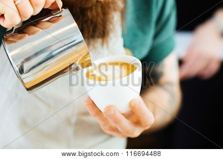 Closeup portrait of barista pouring milk into cup of coffee at the coffee shop