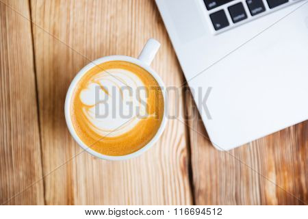 Top view of a cup with cappucino on the wooden table
