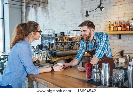 Beautiful young woman in glasses drinking coffee in cafe and talking with handsome barista