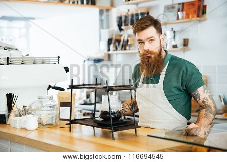 Barista preparing coffee in coffee shop and looking at camera