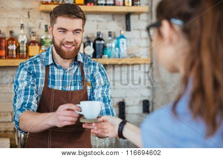 Happy handsome barista in brown apron giving cup of coffee to young woman in coffee shop
