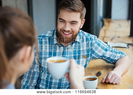 Cheerful young bearded man sitting in cafe and drinking coffee with young woman