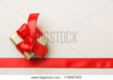 Small Golden Box With Gift Tied Red Bow