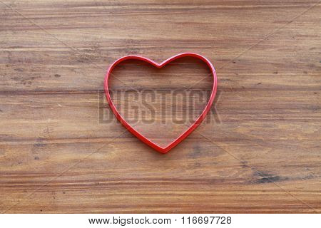 Empty red hollow hearts on a wooden background