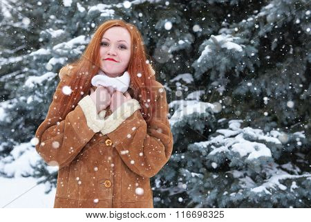 Grimacing redhead woman winter outdoor portrait, snowy fir trees background
