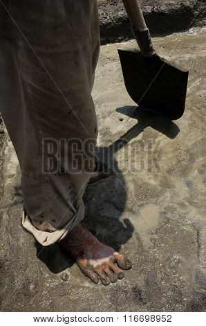 An Indonesian construction worker mixes liquid concrete in bare feet