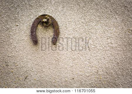 Old Destroyed Concrete Wall With Hanging Horshoe Background