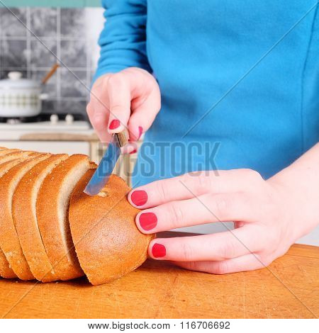 Closeup female hands cutting bread on wooden board