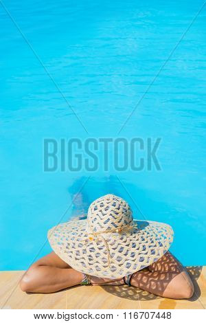 woman in big hat relaxing on the swimming pool