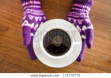 Gloved Hands Holding Cup Of Coffee