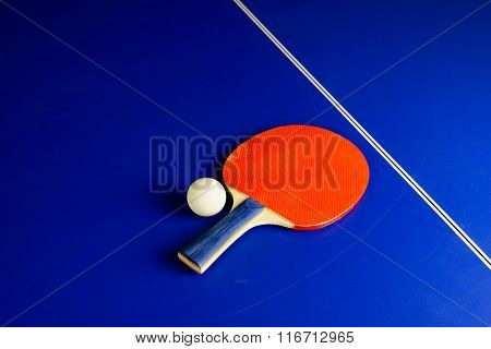 Table Tennis Ball And A Racket On A Blue Table