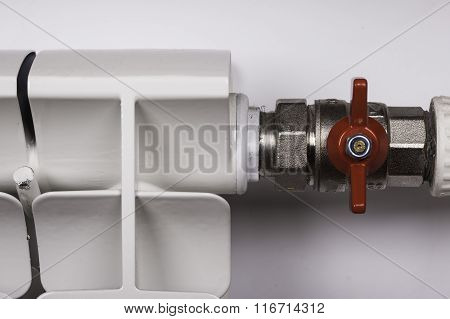 White radiator convector in an apartment faucet valve
