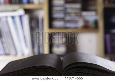 open book on the blured background of bookshelves