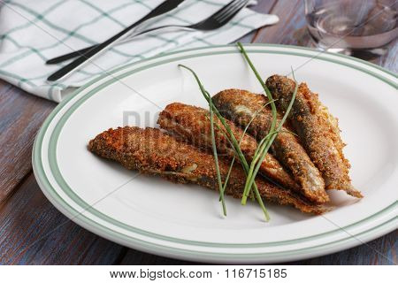Roasted vendace fish on a rustic plate with green onion