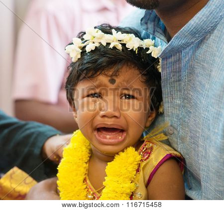 Baby girl crying after karna vedha events. Traditional Indian Hindus ear piercing ceremony. India special rituals.