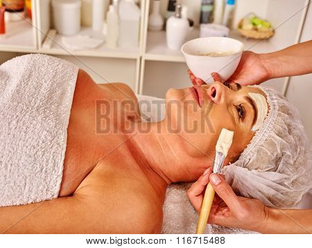 Woman middle-aged take facial and neck anti-aging clay mask in spa salon indoor.