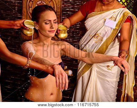 Woman having Ayurvedic spa treatment. Pouring milk treatment.