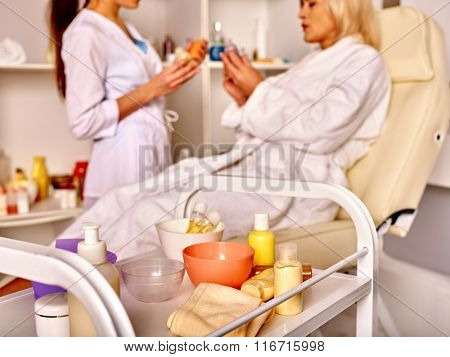 Woman middle-aged having anti-aging procedure in spa salon with young beautician.