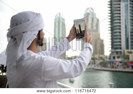 Young Emirati arab man taking photo