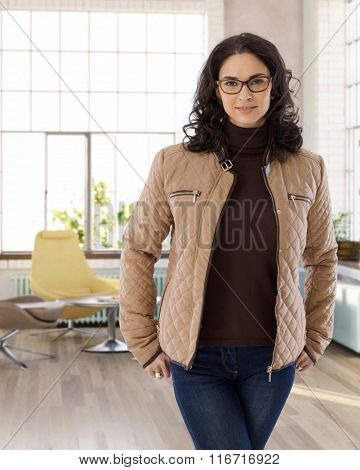 Portrait of attractive young businesswoman standing at home.