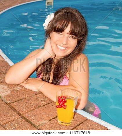 Beautiful woman in a pool with a cocktail next to her