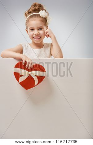 Sweet child girl with white blank poster banner. Happy little girl with gift box. Wedding, Valentine concept.