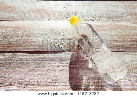 a bottle with water is isolated on a wooden background