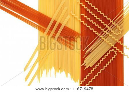 Italian dried tomato and whole wheat pasta forming an abstract background over white with copy space.