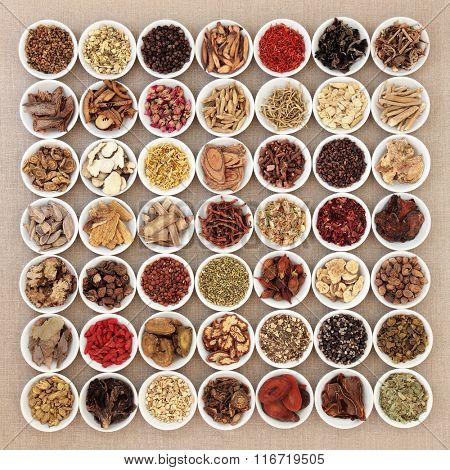Traditional chinese herbal medicine ingredients in white china bowls over hessian background.