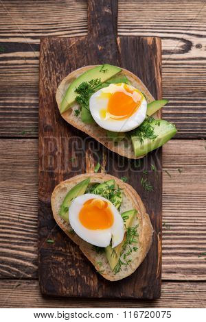 Tasty snack of open sandwich with avocado and soft boiled egg on wooden cutting board. Top view